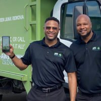 franchise owners holding app on phone in front of junk shot truck